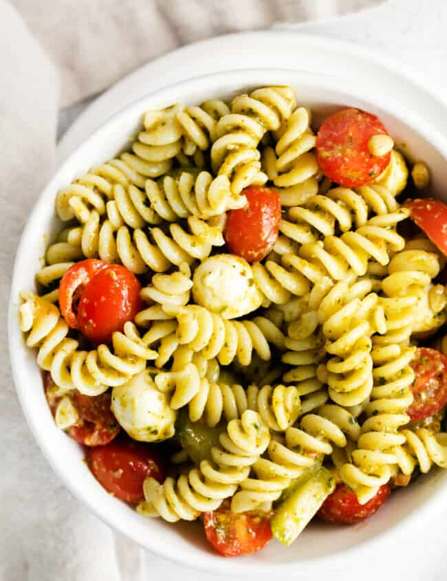 overhead pesto pasta salad in white bowl