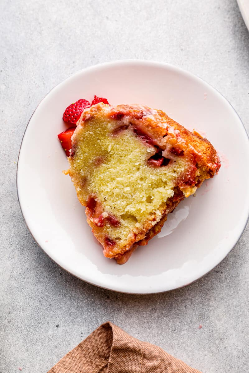 slice of glazed strawberry pound cake on white plate
