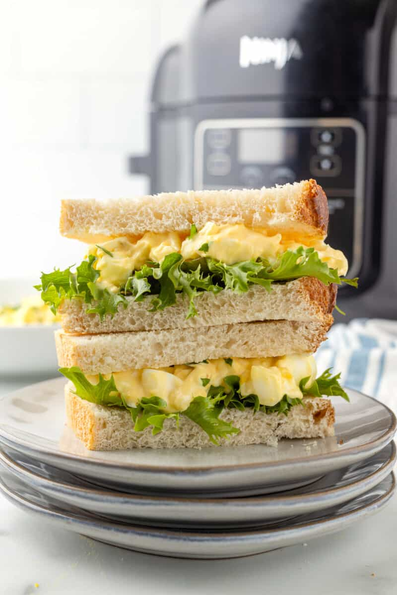 air fryer egg salad sandwiches stacked in front of air fryer