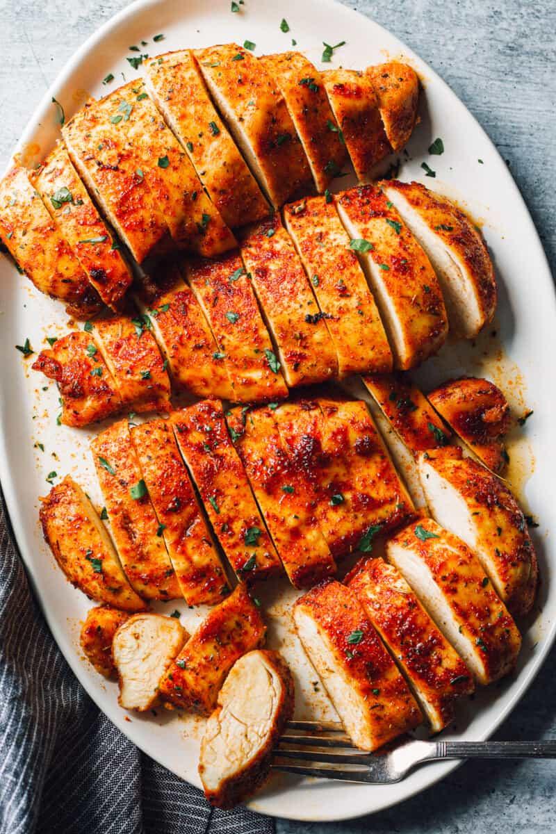 baked chicken breasts sliced on white platter
