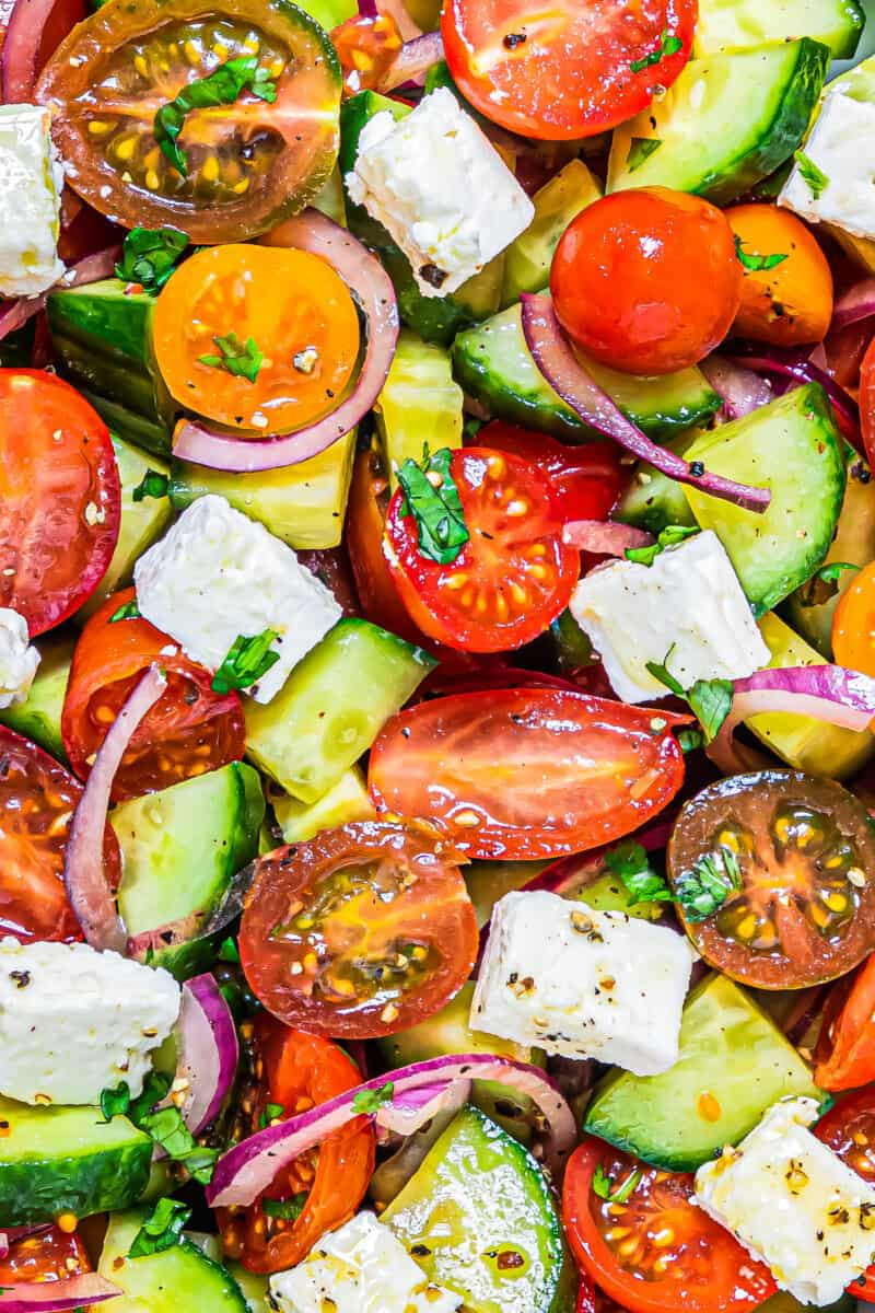 up close cucumber tomato salad in bowl with feta