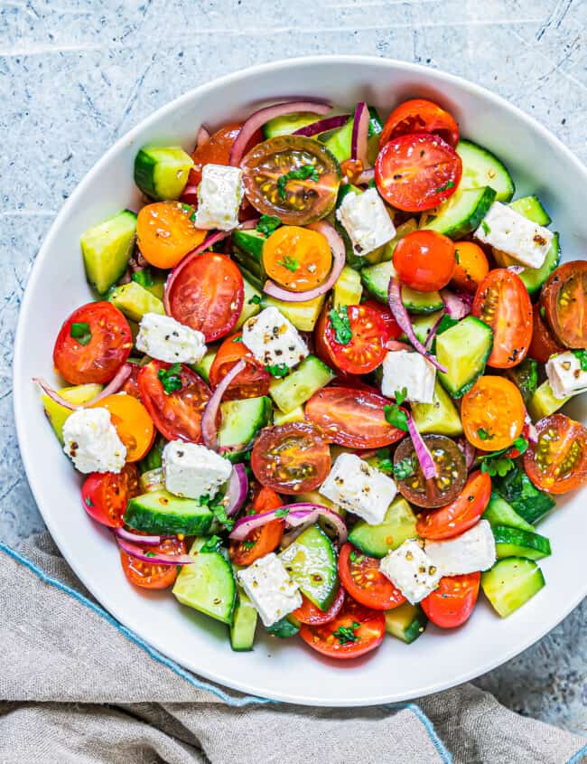 white bowl filled with cucumber tomato salad