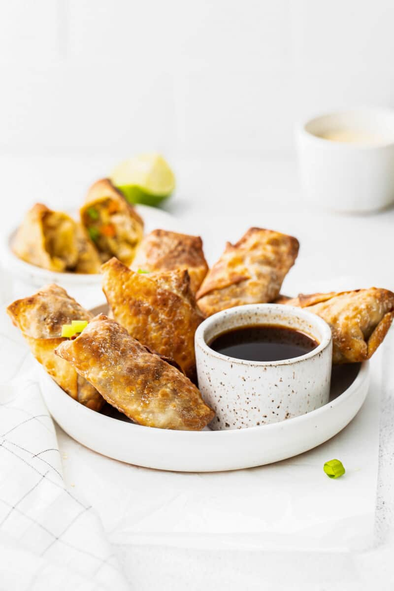 air fryer egg rolls next to bowl of soy sauce