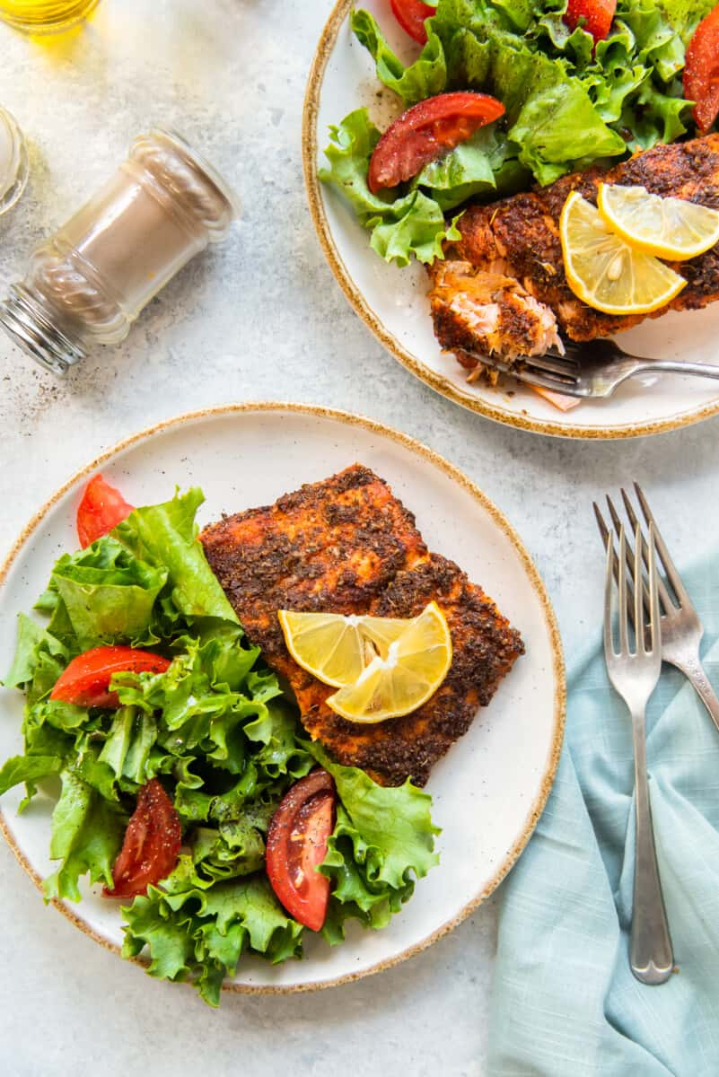 air fried salmon on plates with salad