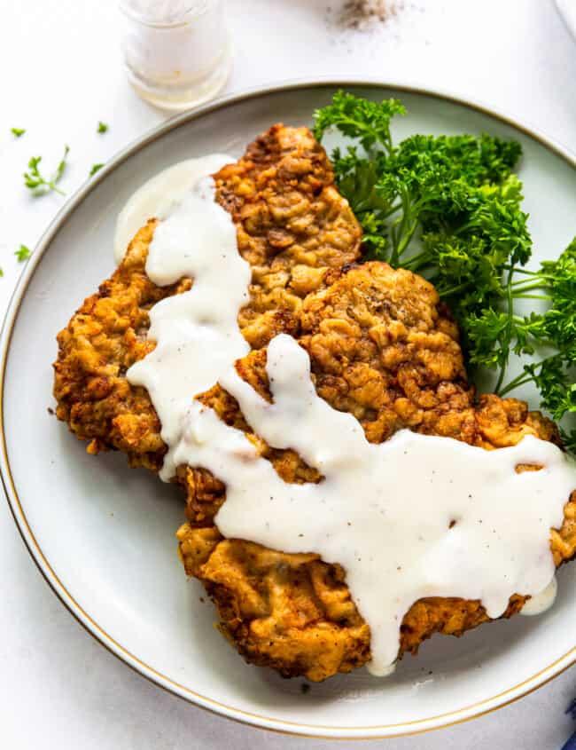 chicken fried steak with gravy on white plate