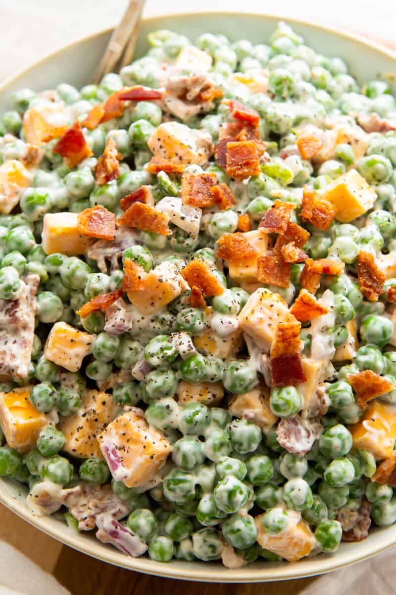 up close bowl of pea salad with cheese and bacon