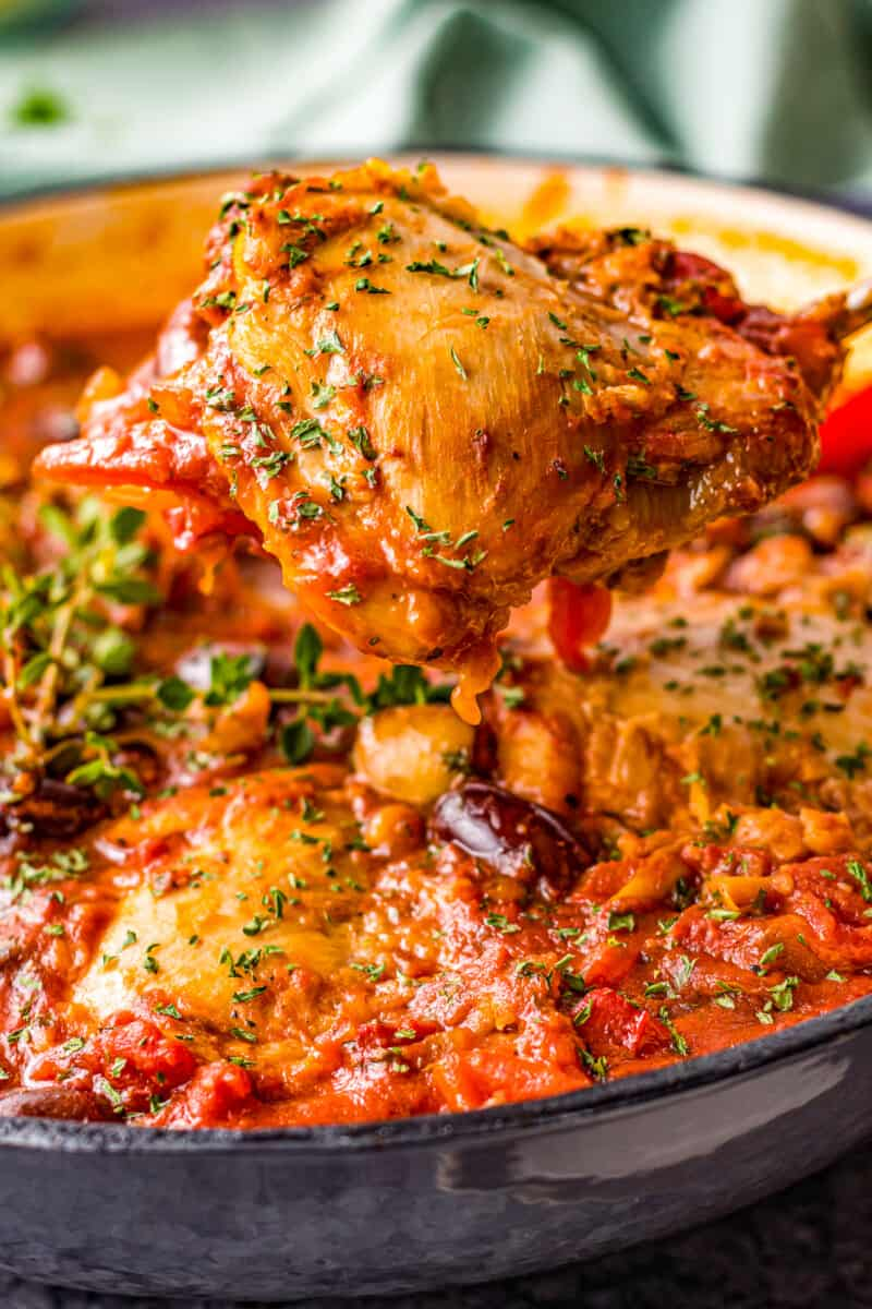 lifting up chicken thigh from pot with chicken cacciatore