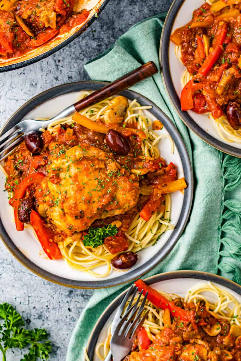 overhead three plates of pasta and chicken cacciatore