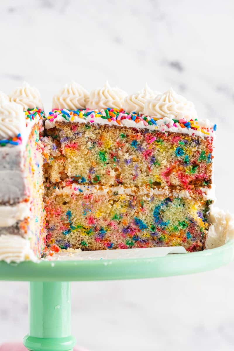 inside of frosted funfetti cake on green cake stand