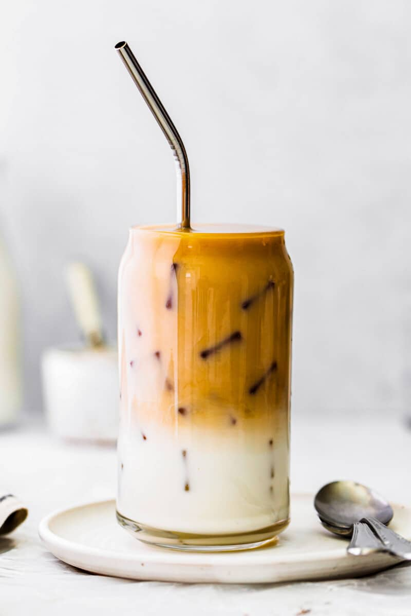 iced chai tea latte in glass cup with metal straw