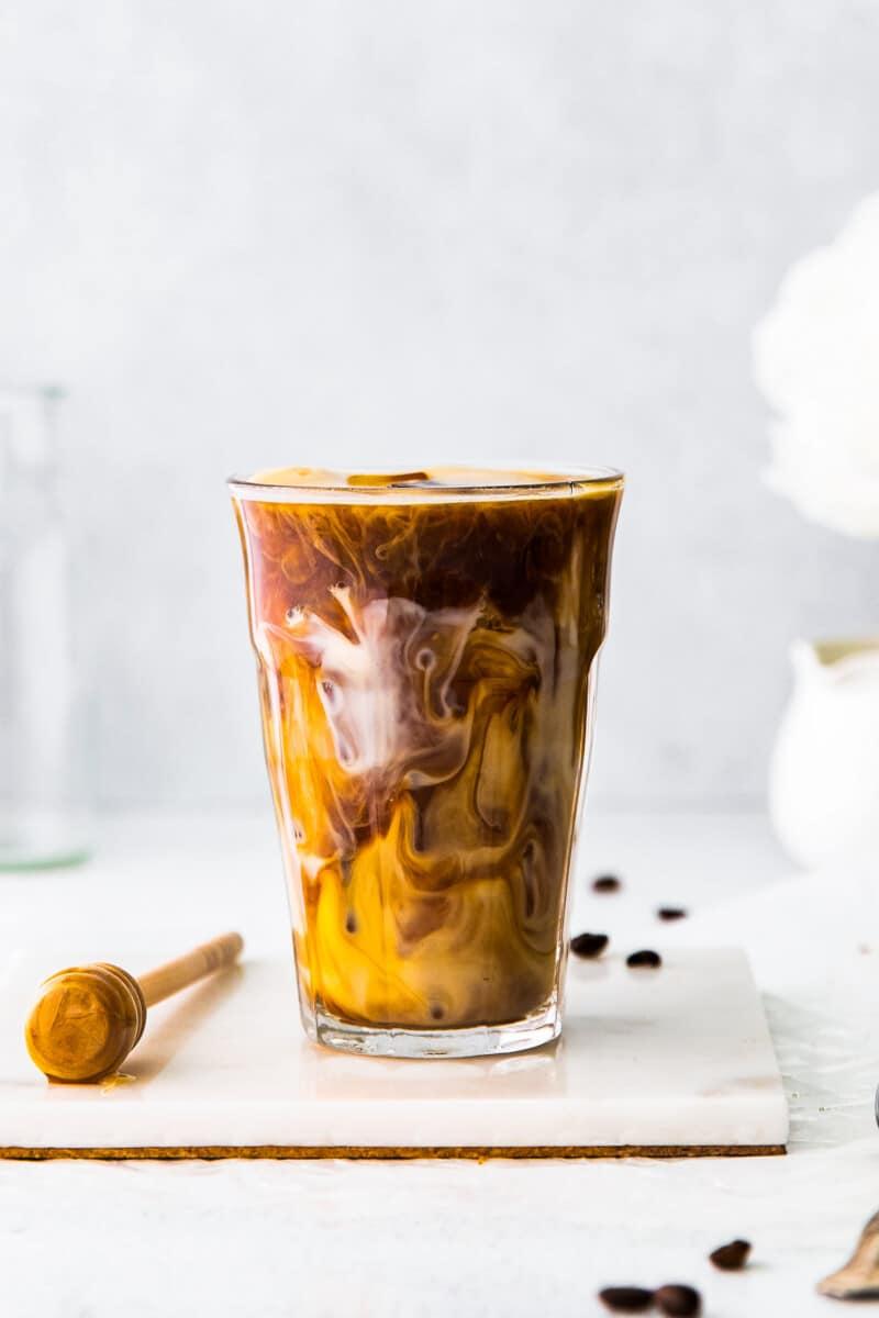 glass filled with honey almondmilk flat white