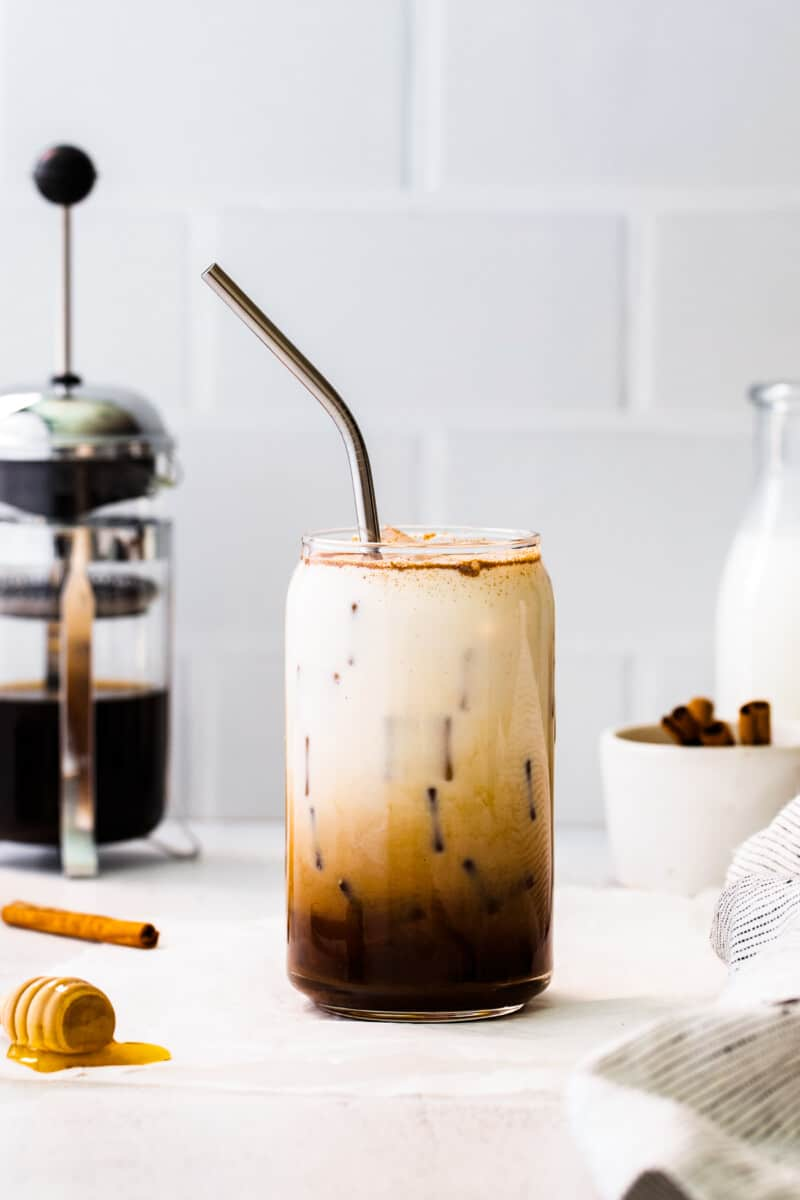 glass of iced honey cinnamon latte with metal straw