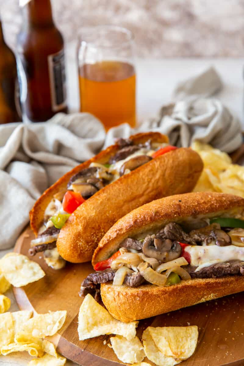 two philly cheesesteaks on cutting board