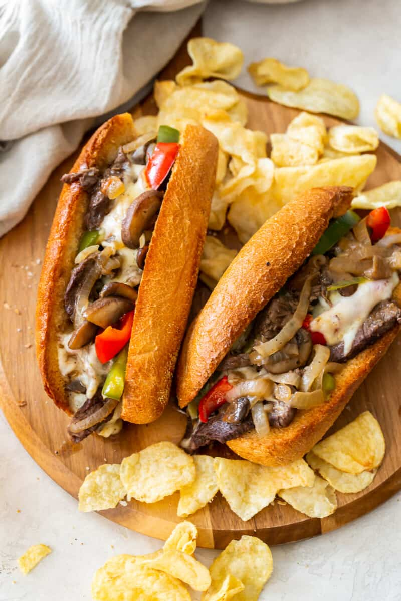 overhead two philly cheesesteaks on cutting board