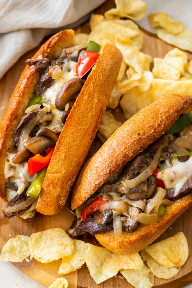 two philly cheesesteaks on cutting board with chips