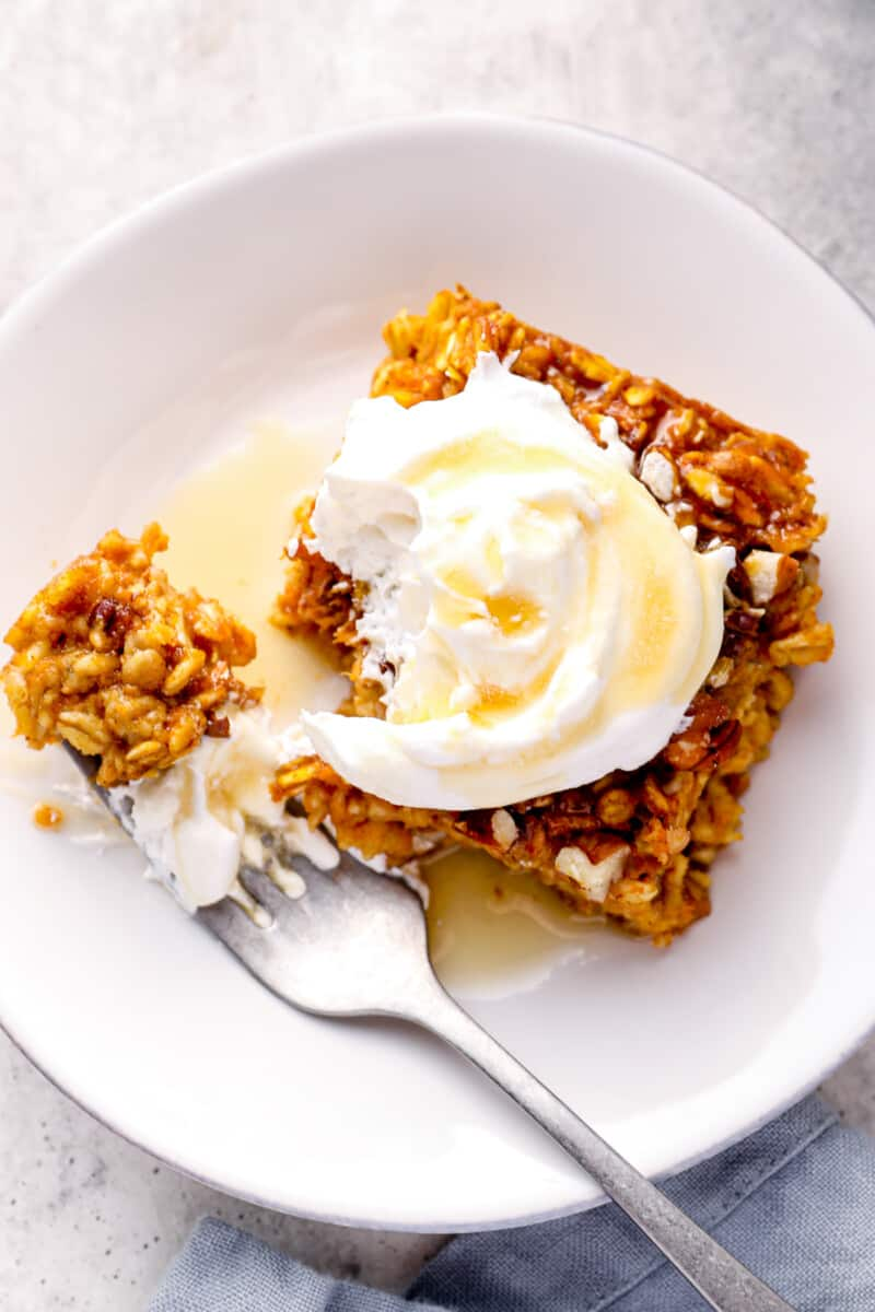 slice of pumpkin pie baked oatmeal with whipped cream and maple syrup