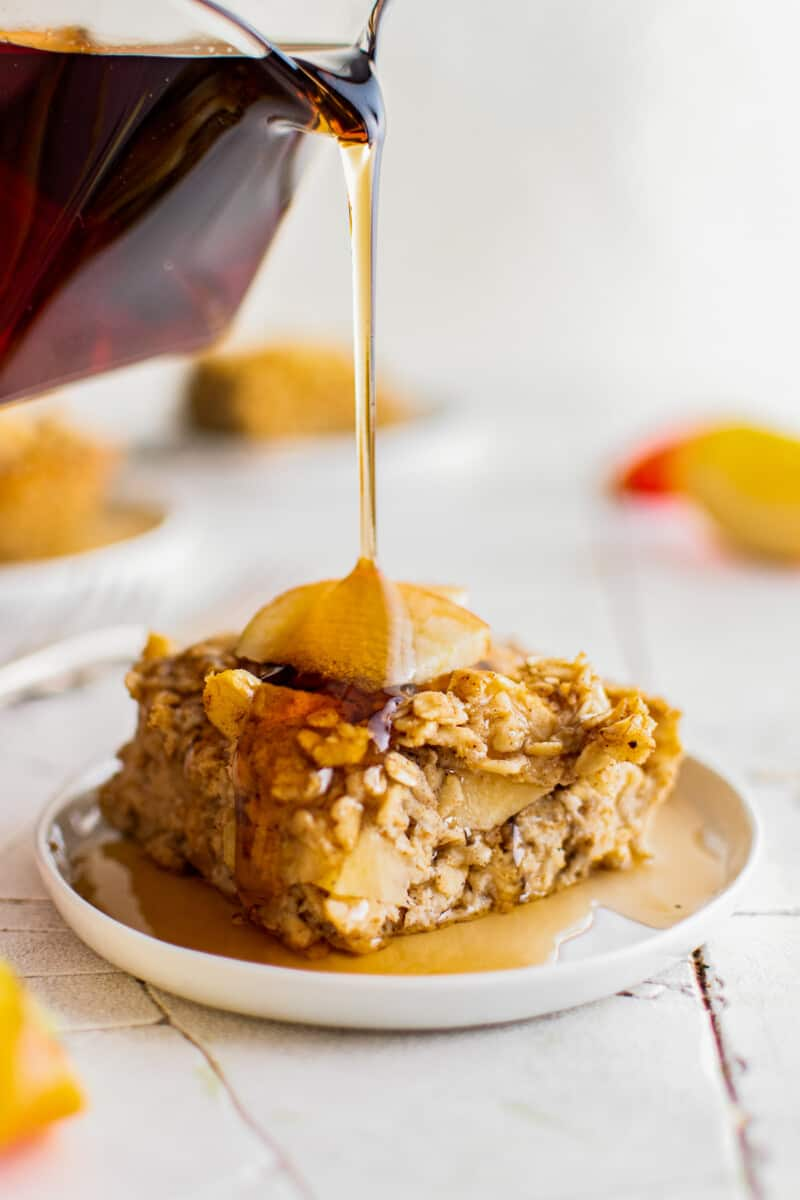drizzling maple syrup on baked apple oatmeal