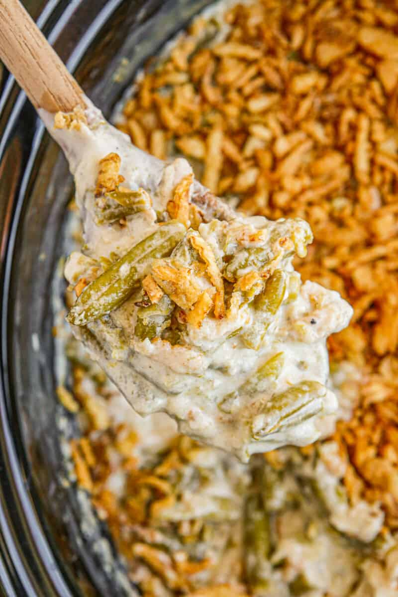 holding wooden spoon up with crockpot green bean casserole