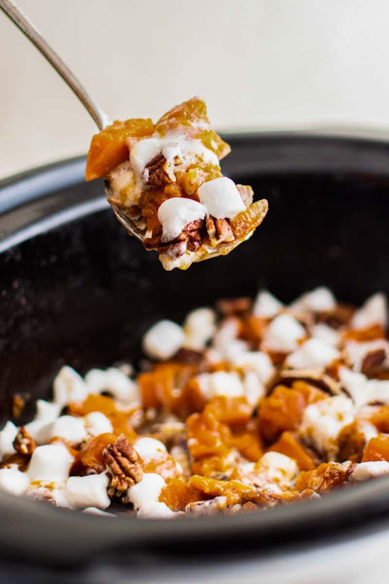lifting up forkful of sweet potato casserole from crockpot