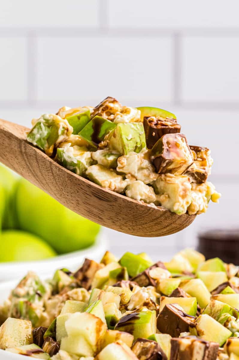 wooden spoon lifting up snickers apple salad