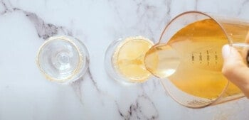 pouring apple cider into a champagne glass