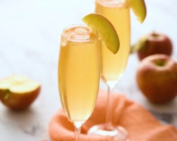 2 apple cider mimosas in glass champagne flutes garnished with apple slices