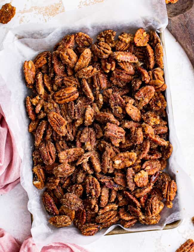 overhead image of candied pecans on a baking sheet lined with parchment paper
