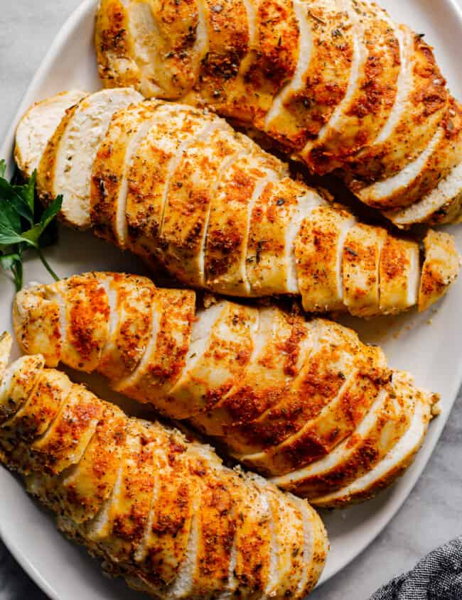 overhead sliced crockpot chicken breasts with spice rub on white plate