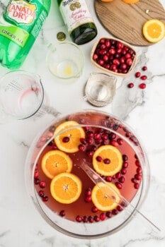 overhead image of holiday punch in a glass bowl with orange slices and cranberries