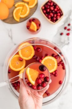 overhead image of hand holding a glass of holiday punch over a punch bowl