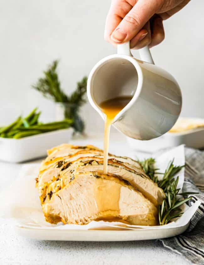hand pouring gravy onto slices of garlic herb turkey breast